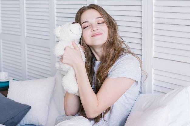 朝の寝室のベッドに座っている美しい若い女性