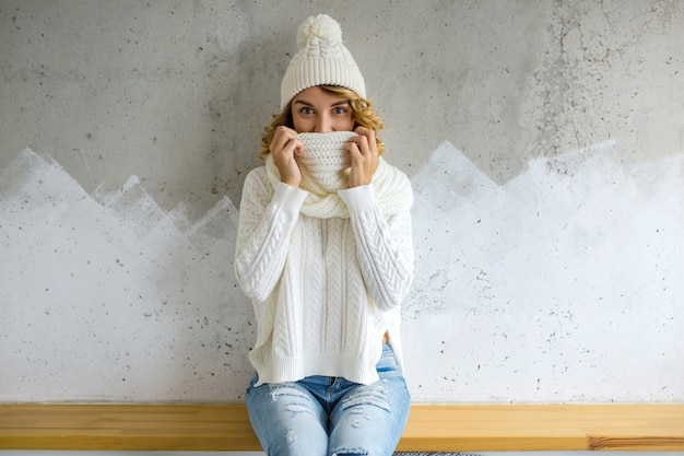 Beautiful young woman sitting against wall wearing white sweater, knitted hat and scarf