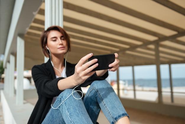 座って、ビーチのベランダで携帯電話から音楽を聴いて美しい若い女性