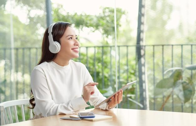 テーブルに座ってオーディオブックを聞いている美しい若い女性