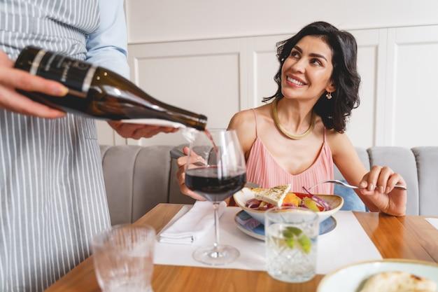 カフェの労働者がワイングラスにアルコール飲料を注いでいる間、おいしい料理とテーブルに座っている美しい若い女性