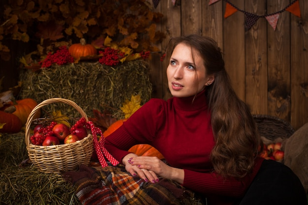 Beautiful young woman sitting in autumn setting on hay with a basket of apples and rowan
