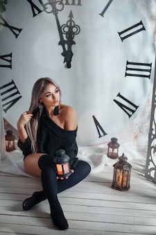 Beautiful young woman sitting on the background of a large clock