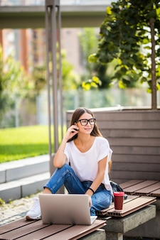 Beautiful young woman sitting on bench holding coffee while using laptop outdoor.