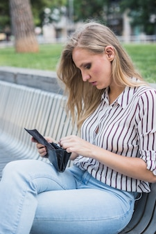 Beautiful young woman sitting on bench looking at wallet