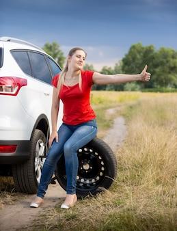 Beautiful young woman sitting at broken car and hitchhiking at field