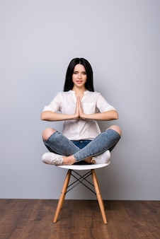 Beautiful young woman sitting on chair in lotus pose against gray space