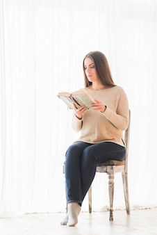 Beautiful young woman sitting on chair reading book