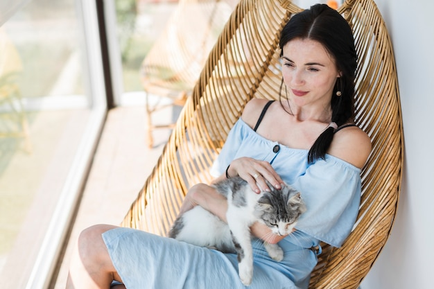 Beautiful young woman sitting on chair with her cute cat