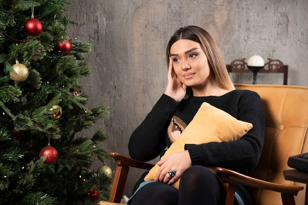 Beautiful young woman sitting next to christmas tree.
