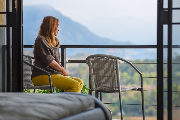 Beautiful young woman sitting on hotel balcony of the bedroom to enjoying sunrise landscape view.