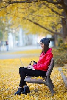 아름 다운 젊은 여자는 벤치에 앉아서가 그녀의 노트북을 사용 하여.