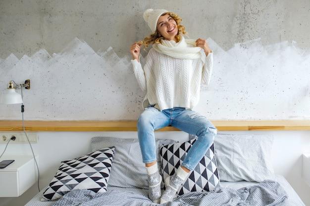 白いセーターを着て壁に寝室に座っている美しい若い女性