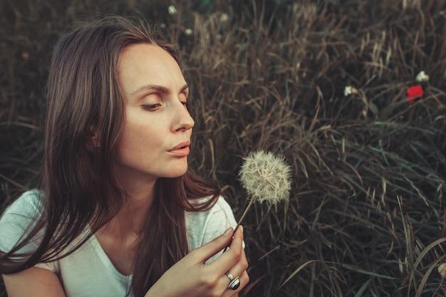 푸른 잔디에 앉아서 민들레를 불고 아름 다운 젊은 여자. 옥외. 자연을 만끽할. 봄 잔디에 건강한 백인 소녀입니다. 알레르기 무료 개념입니다. 빈티지 필터