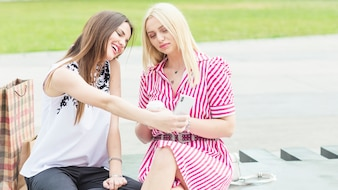 Beautiful young woman sitting in park taking selfie with cellphone