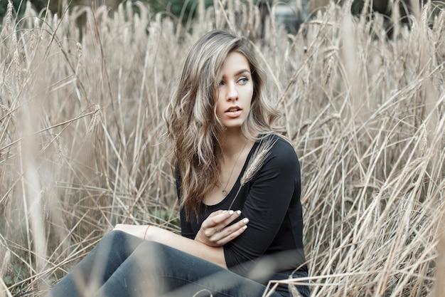 乾いた草に座っている美しい若い女性。小麦畑