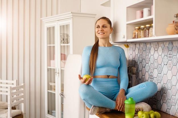 台所に座って、手に青リンゴを持っている美しい若い女性。フィットネスのトラックスーツを着た女性。ホームスポーツのコンセプト。