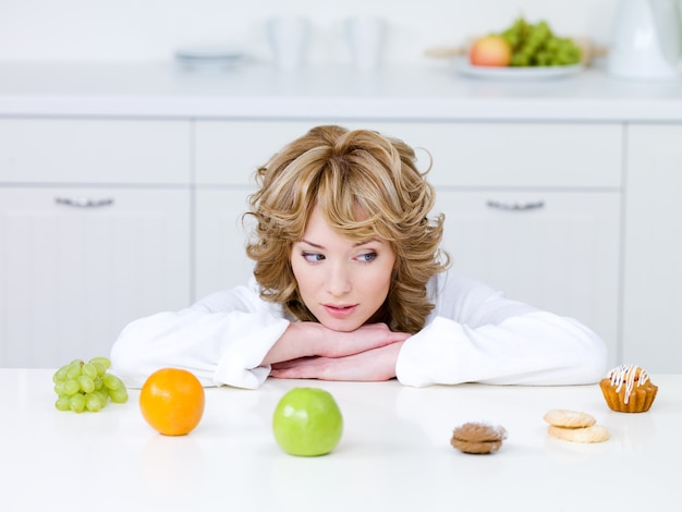 Bella giovane donna seduta in cucina e scegliendo tra frutti sani e gustose torte