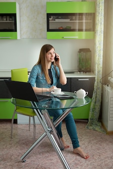 Beautiful young woman sitting in the kitchen at the table with a laptop drinking tea and talking on the phone