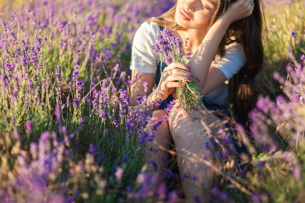 Beautiful young woman sitting in a meadow with a bouquet of lavender and dreaming in the sunset rays