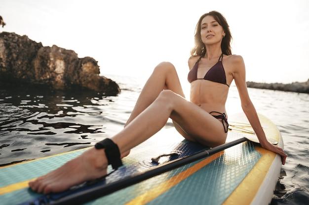 Красивая молодая женщина, сидящая на доске с веслом в море