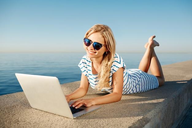 ラップトップとビーチに座っている美しい若い女性