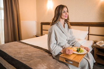 Beautiful young woman sitting on bed in hotel room enjoying the healthy breakfast