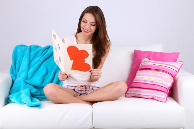 Красивая молодая женщина, сидя на диване с картой на сером фоне