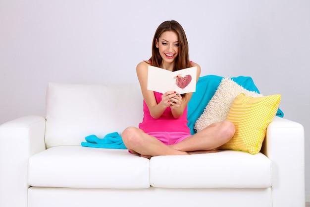 灰色の壁にカードとソファに座っている美しい若い女性