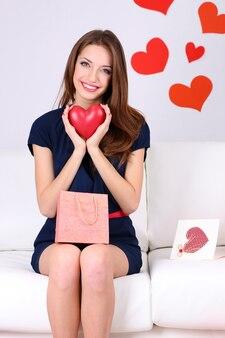 Красивая молодая женщина, сидя на диване с хозяйственными сумками на сером фоне