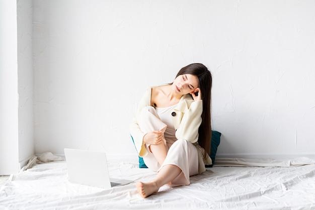 아름 다운 젊은 여자는 바닥에 앉아 멀리보고 노트북에 프리랜서 프로젝트를하고