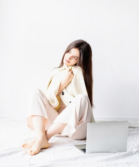 아름 다운 젊은 여자는 바닥에 앉아 컴퓨터를 사용 하여 노트북에 프리랜서 프로젝트를 수행