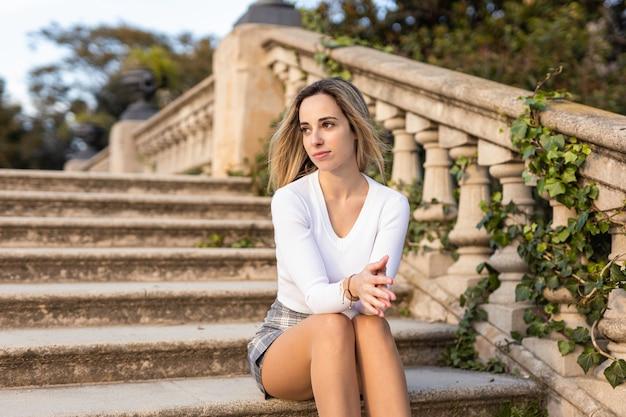 階段に座っている美しい若い女性
