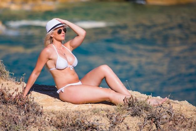 海岸の石の上に座っている美しい若い女性