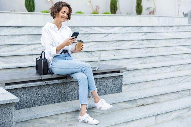 Красивая молодая женщина, сидящая на открытом воздухе на улице