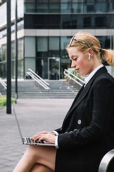 ラップトップに入力する事務所ビルの外に座っている美しい若い女性