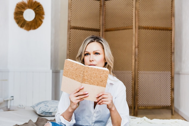 Beautiful young woman sitting on the sofa in light clothes, writing in a notebook