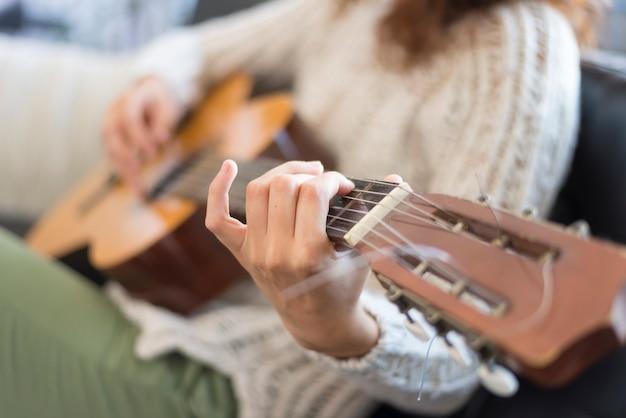 Beautiful young woman sitting on sofa playing guitar