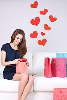 Beautiful young woman sitting on sofa with shopping bags