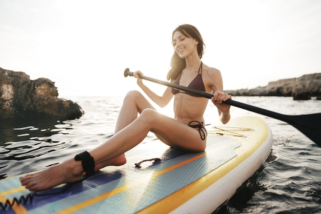 Beautiful young woman sitting on a stand up paddle board in sea