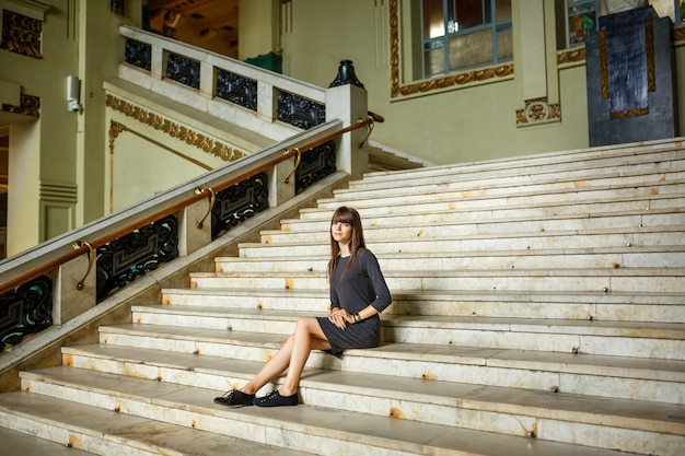Beautiful young woman sitting on the steps