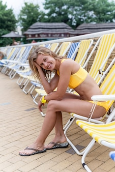 The beautiful young woman sitting on the sun lounger next to the pool