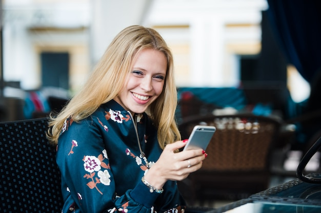 Beautiful young woman sitting in trendy outdoors urban coffee shop, smiling and texting message on her smartphone. horizontal