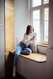Bella giovane donna che si siede sull'ampia finestra in blue jeans e maglietta bianca