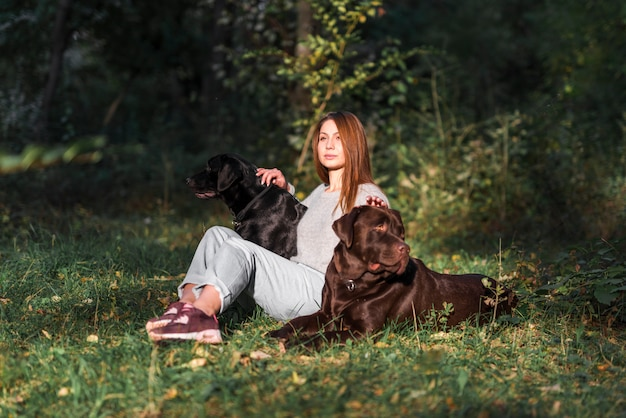 Beautiful young woman sitting with her pets in park