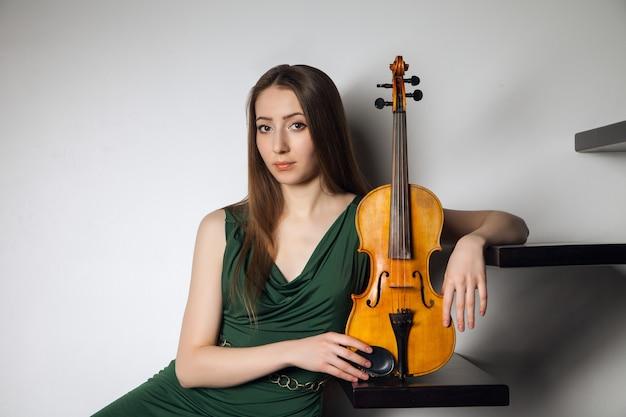 Красивая молодая женщина, сидя со скрипкой на лестнице на белом фоне