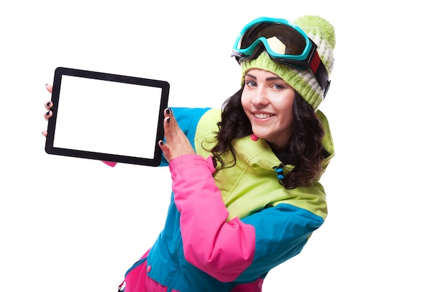 Beautiful young woman in ski outfit and ski goggles hold empty tablet