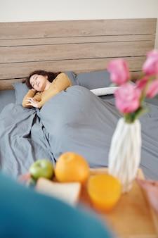 Красивая молодая женщина спит в постели, когда муж приносит ее поднос с завтраком и цветами