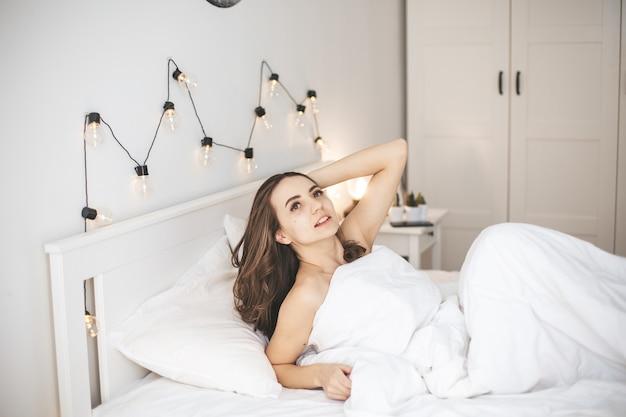 Красивая молодая женщина, спящая в удобной кровати на белых свежих простынях. женское лицо просыпается утром с открытыми глазами. концепция здорового сна.