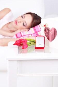 Красивая молодая женщина спит на диване возле стола с подарками и цветами, крупным планом